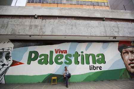 caracas: CARACAS, VENEZUELA, APRIL 20: Unidentified man sitting on a chair outside in the street of Caracas in downtown. There is a painting of Chavez and Viva Palestina written in the background.