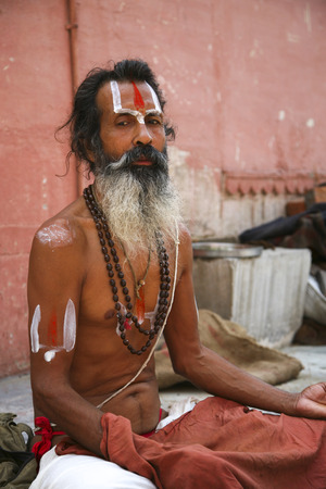 alleged: Varanasi, India - June 1, 2009: Unidentified sadhu sitting and meditating on ghat along the Ganges on June 1, 2009 in Varanasi, India. Tourism has drawn many alleged fake sadhus to Varanasi. Editorial