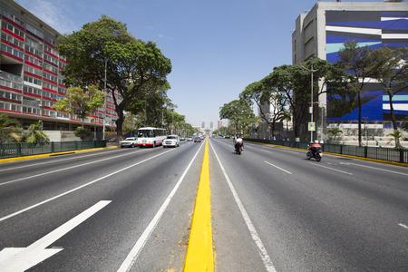 CARACAS, VENEZUELA, 20 APRIL: Weg met klein verkeer, bus, auto's en moto's, vroeg in de ochtend in Caracas tegen een blauwe hemel, Venezuela 2015.