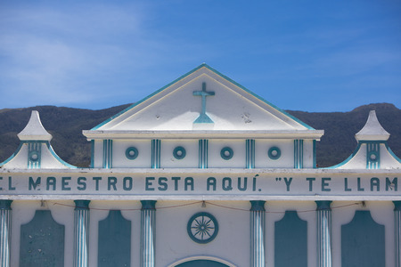 colonial church: Little small blue and white small colonial church against a clear blue sky with a cross, basic decoration and letters on the facade. Merida State Venezuela