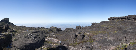 volcanic stones: Landscape at the top of Mount Roraima in the morning with blue sky. Unrecognizable hiker walking through the black volcanic stones, and endemic plants. Gran Sabana. Venezuela 2015. Stock Photo