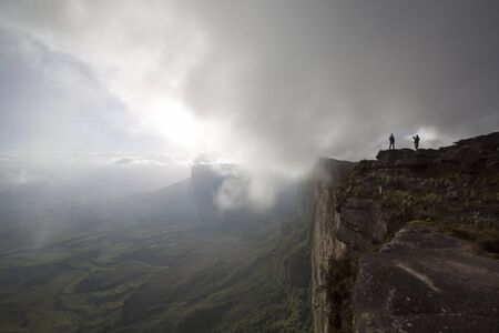 koreans: Two people taking photos at the top of Mount Roraima in the clouds. The view is breathtaking on the Gran Sabana. Venezuela 2015. Stock Photo