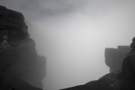 koreans: MOUNT RORAIMA, VENEZUELA, APRIL 3: Panorama of wild landscape at the top of Mount Roraima with fog a 600m cliff and two unidentified Koreans tourists. Gran Sabana. Venezuela 2015.