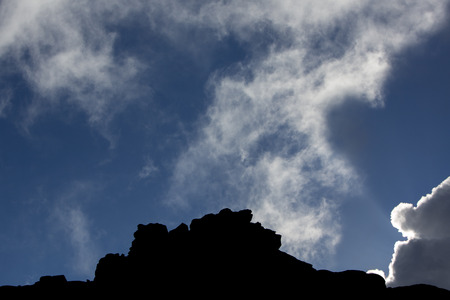 mistery: The silhouette of the cliffs of Kukenan tepui or Mount Roraima  with clouds and blue sky. Gran Sabana. Venezuela 2015.