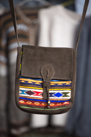 artisanry: Handmade wool and leather bag for sale at the outdoor craft market in Otavalo. Ecuador is written on the bag. Editorial