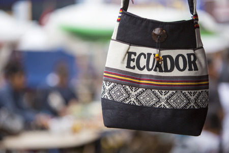 artisanry: Handmade wool bag for sale at the outdoor craft market in Otavalo. Ecuador is written on the bag.
