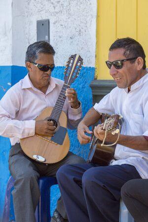 latina america: TRUJILLO, PERU, JANUARY 25: Unidentified blind Peruvian musicians playing guitar outside in the street of Trujillo - Peru 2015