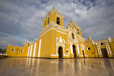 exterior wall: Magnificent yellow cathedral with a beautiful blue sky and light reflections in Trujillo, Peru Editorial