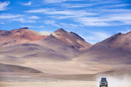 lipez: Off-road vehicle driving in the Atacama desert, Bolivia with majestic colored mountains and blue sky in Eduardo Avaroa Andean Fauna National Reserve, Bolivia