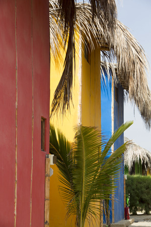 manora: Detail of colored wooden houses standing on the beach with Palm trees, Punta Sal near Mancora, Peru. Stock Photo