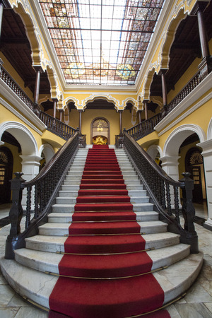 view of a wooden doorway: Yellow colonial interior and marble staircase with red carpet at Archbishops Palace in Lima during the day, Peru