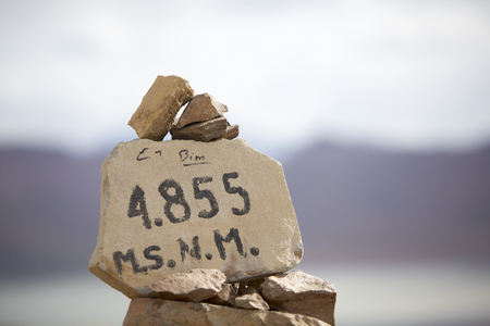 lipez: Pile of stones with the altitude of 4855 meters above the sea levels. Eduardo Avaroa National Park. Bolivia. (Selective focus on the numbers) Stock Photo