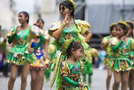 south american ethnicity: SALTA, ARGENTINA, DEC 18: Young women performers dancing and celebrating the opening of the carnival of Salta in the street with colorful costumes. North of Argentina 2014 Editorial