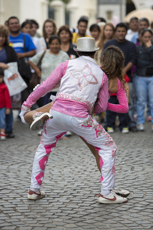 south american ethnicity: SALTA, ARGENTINA, DEC 18: Young couple performers dancing and celebrating the opening of the carnival of Salta in the street with colorful costumes. North of Argentina 2014 Editorial