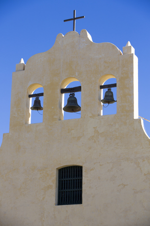 colonial church: Close up of a colonial church with tree bells and a cross against a clear blue sky in Cachi small town within Calchaqui Valleys in Salta Province. Argentina Stock Photo