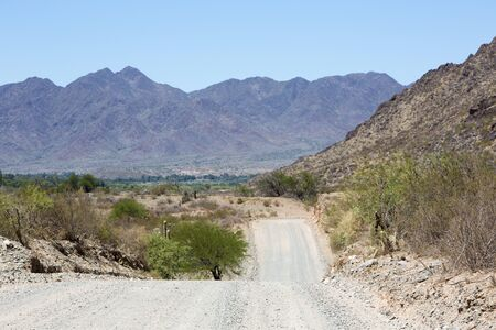 ruta: The famous Route 40 gravel road parallel to the Andes against a blue sky and going to Cafayate. Ruta 40 within the Calchaqui Valleys in Salta Province. Argentina