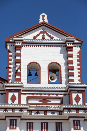 the church of our lady: Colorful white church Our Lady of Carmen on the square with blue sky in village of Guatape near Medellin, Colombia.