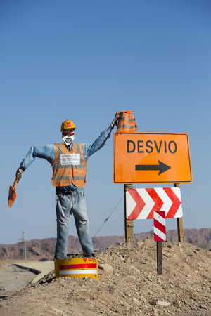 roadwork: Fake traffic mannequin standing on the famous Ruta 40 (Route 40) with clear blue sky and giving new direction while the road is under construction. San Juan Province. Argentina