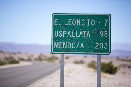 mendoza: Old distance sign road on paved road with blue sky on the famous Ruta 40 (Route 40). Direction to Mendoza, Uspallata and El Leoncito. San Juan Province Argentina