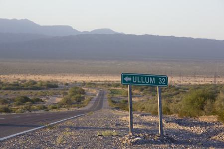 Camino viejo signo de la distancia en la carretera pavimentada con el cielo azul y la puesta de sol en la famosa Ruta 40 (Ruta 40). Dirección de Ullum. Provincia de San Juan Argentina Foto de archivo