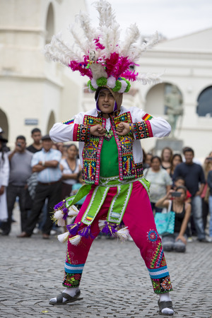 south american ethnicity: SALTA, ARGENTINA, DEC 18: Young adult performer dancing and celebrating the opening of the carnival of Salta in the street with colorful costumes. North of Argentina 2014