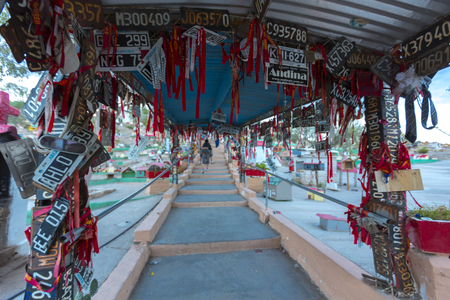 deceased: VALECITO, ARGENTINA, DEC 15: The entrance stairs to the Deceased Correa in Spanish Difunta Correa pilgrimage landmark in San Juan Province, with many offerings and registration plates from all over the world. Argentina 2014