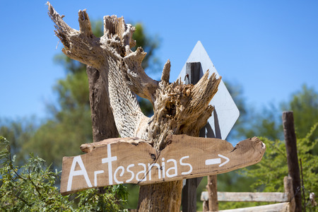 sign post: Wooden sign post on dried cactus with Artesanias written in Spanish or crafts in English, blurred blue and green nature background. Cafayate, Salta Province. Argentina Stock Photo