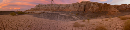 geological formation: Panorama of pink and red colored sunset with geological rock formation at Rodeo with cracks on the pan - Near the Lake of Wind (Dique del Viento) in San Juan Province, Argentina