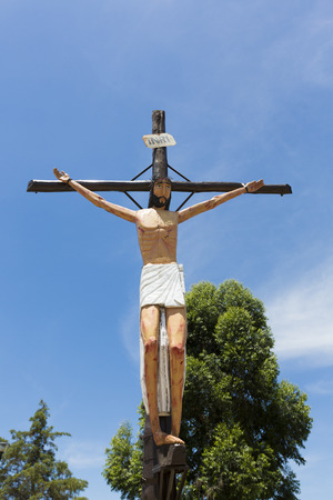 wine road: CACHI, ARGENTINA, DEC 26: Crucified retro styled christ statue against blue sky on the Wine road to Cafayate coming from Salta. Argentina 2014 Editorial
