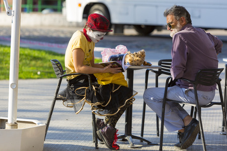 face centered: Caucasian young man disguised as a clown reading a book and sitting at an outdoors table with an older man. Lifestyle in the cultural city of Buenos Aires. Argentina 2014 Editorial