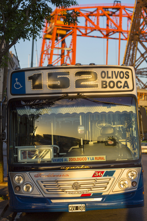 busbar: Urban public bus 152 in La Boca with Nicolas Avellaneda bridge in the background early in the morning. Buenos Aires. Argentina 2014