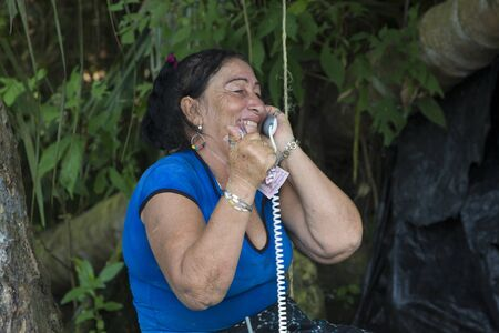 bogs: Happy senior woman holding money in one hand and a phone dans lautre hand, bogs near Juan Manuel National Park. Maracaibo Lake, Venezuela 2015