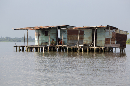 bogs: Fisher men sitting outside Lifted up poor wooden houses standing on the lake Maracaibo and looking in the camera. Bogs Juan Manuel National Park. Maracaibo Lake, Venezuela 2015