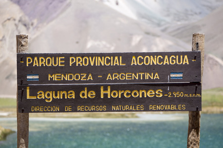 aconcagua: Welcome wooden sign at the Aconcagua National Park with turquoise lake in the background. Andes Mountains, Argentina (selective focus) Editorial
