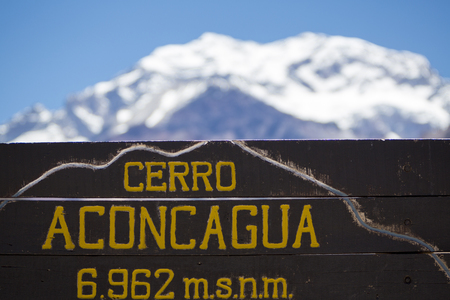 aconcagua: Welcome wooden sign at the Aconcagua National Park with the peak of the mountain at 6962 meters above sea level and a clear blue sky in the background, Andes Mountains, Argentina