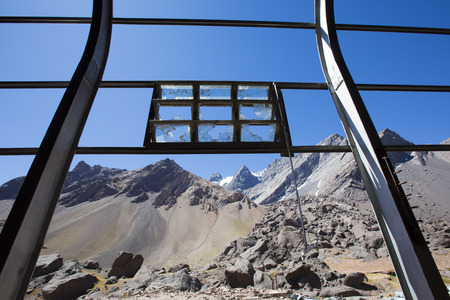 urban decline: Old Industrial iron window frame rusting with broken glass at abandoned train station at the border with Argentina and Chile. Mountains and blue sky in the background. Stock Photo