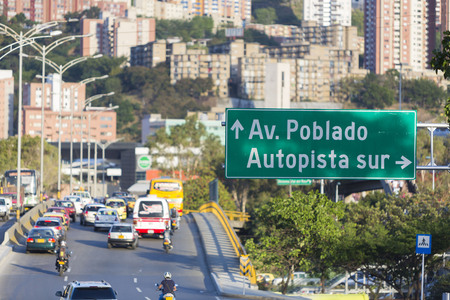 antioquia: MEDELLIN, COLOMBIA, MARCH 11: Cityscape and road sign pointing the direction to Poblado district with traffic on the road. Medellin, Colombia 2015 (selective focus)
