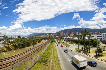 medellin: Outdoors view of the Medellin metro line with railway tracks and cityscape with traffic on the road. Colombia 2015