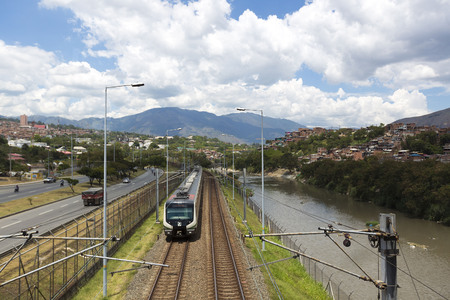 medellin: Outdoors view of the Medellin line with metro train, railway tracks, river and cityscape with traffic on the road. Colombia 2015