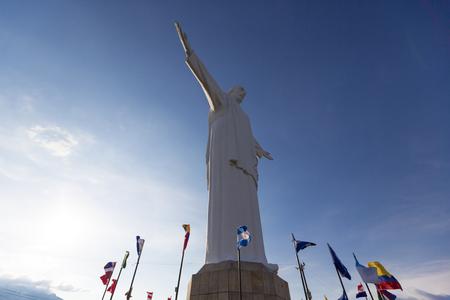 bandera de colombia: Vista frontal del Cristo del Rey estatua de Cali contra un cielo azul con banderas internacionales ondeando alrededor. Colombia
