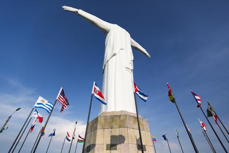 Rückansicht des Cristo del Rey Statue von Cali gegen einen blauen Himmel mit internationalen Fahnen schwenkten herum. Kolumbien Standard-Bild