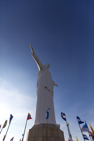 Side view of Cristo del Rey statue of Cali against a blue sky with international flags waving around. Colombia Stock Photo