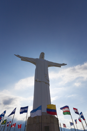 Front view of Cristo del Rey statue of Cali against a blue sky with international flags waving around. Colombia Stock Photo