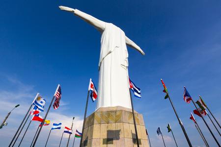 Rückansicht des Cristo del Rey Statue von Cali gegen einen blauen Himmel mit internationalen Fahnen schwenkten herum. Kolumbien