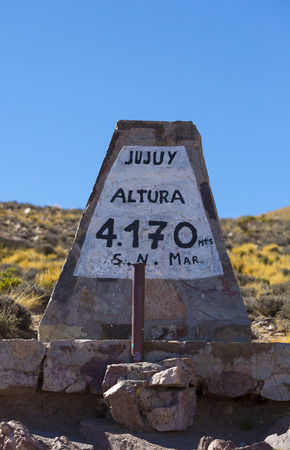 ruta: Stone mountain pass sign at 4170 meters written in Spanish with blue sky in Jujuy Province, Argentina