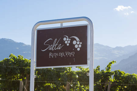wine road: SALTA, ARGENTINA, DEC 17: Welcome sign road on the Salta Ruta Del Vino written in Spanish or Route of the Wine with vineyards and blue sky in the background. Salta Province. Argentina