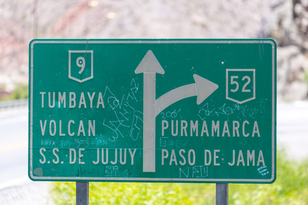 bidirectional: Road sign to Purmamarca or S.S. De Jujuy, Argentina with arrows pointing to right and top sides of frame, nice blurred light trees background. Stock Photo