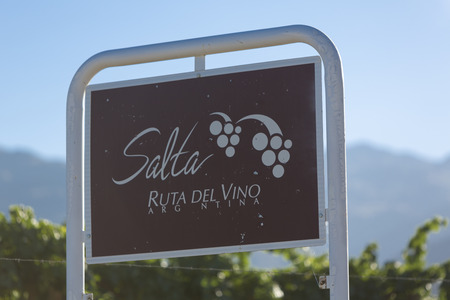 wine road: Welcome sign on the road Salta Ruta Del Vino written in Spanish gold of the Wine Route with vineyards and blue sky in the background. Salta Province. Argentina Stock Photo