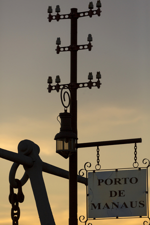 amazonas: Silhouete of old electric pylons and signboard with Porto de Manaus written in Portuguese (harbor of Manaus) during a sunset in Manaus, Amazonas State. Brazil