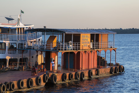 amazonas: Panorama and sunset of typical wooden red and white boat passengers Amazon anchored at the harbor of Manaus, Amazonas State. Brazil 2015